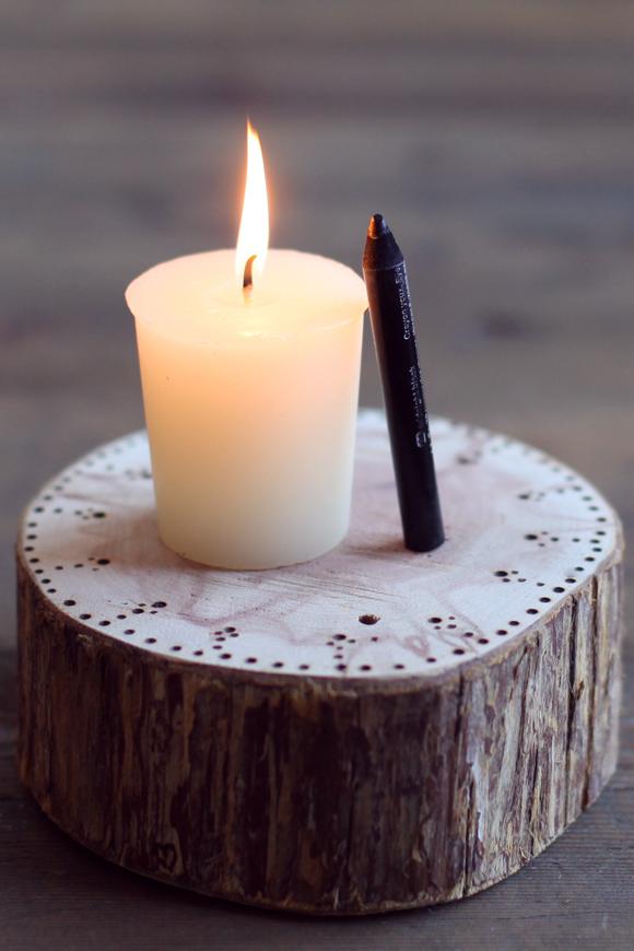 Eyeliner-and-candle-on-wood-stump